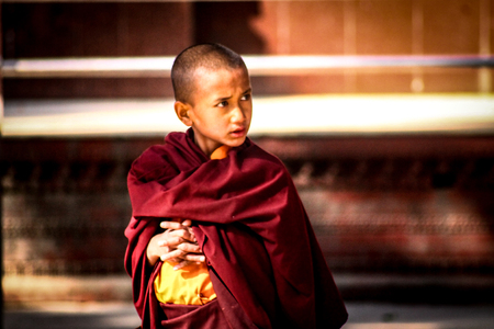 A young Buddhist monk with folded hands on the Swayambhunath temple complex