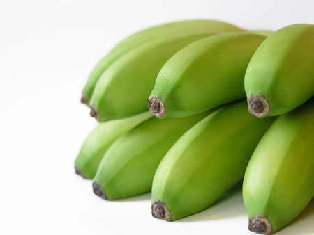 A close up of a bunch of green dominican bananas on a white background