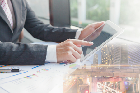 Double exposure businessman using the tablet in office with cityscape and financial graph on blurred building background, Business Trading concept.