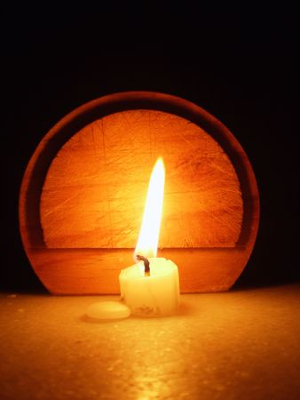 Candle in front of a wood circle