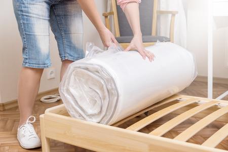 Photo pour Woman unrolling new mattress - image libre de droit