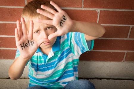 Photo for A pre-teen boy is begging to help him showing the message written on his palms - Royalty Free Image