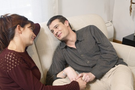 Young couple talking on a sofa.