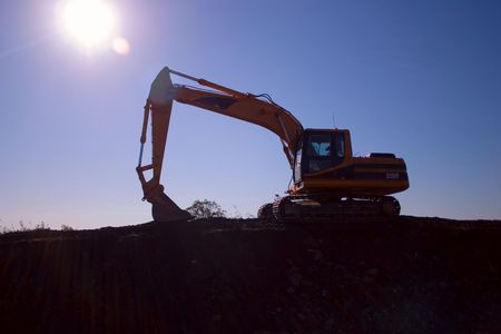 Digger silouette against sun
