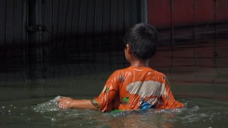 LAMLUKKA (PATHUMTHANI), THAILAND – CIRCA NOVEMBER 2011 – An unidentified solitary boy wades through a flooded road circa November 2011 in Lamlukka. The entire province has been flooded as a result of an exceptional and unprecedented rainy season.