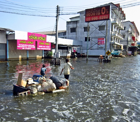 LAMLUKKA (PATHUMTHANI), THAILAND – CIRCA NOVEMBER 2011 – Two unidentified people pull an improvised raft with some goods through a flooded road circa November 2011 in Lamlukka. The entire province has been flooded as a result of exceptional rainfall.
