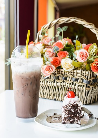 Ice chocolate with chocolate cake on table