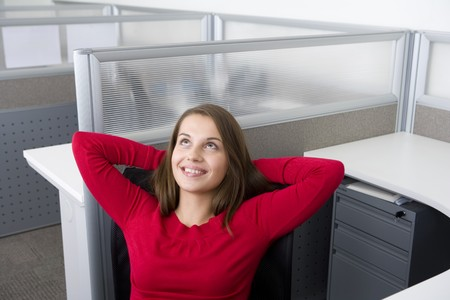 Businesswoman relaxing in office cubicle