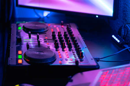 Photo for dj table with headphones mixing music flashy colors blue purple - Royalty Free Image