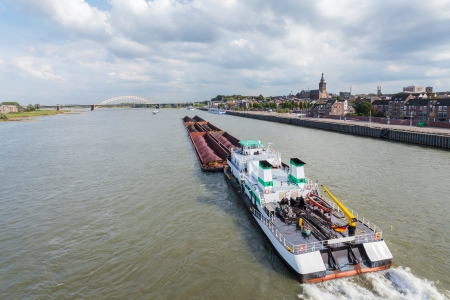 Cargo riverboat passing the Dutch city Nijmegen on the river Waal