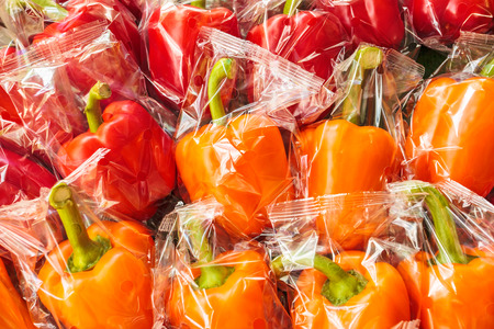 Bunch of plastic wrapped orange and red bell peppers