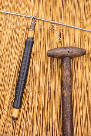 Traditional thatch tools in front of a newly thatched roof