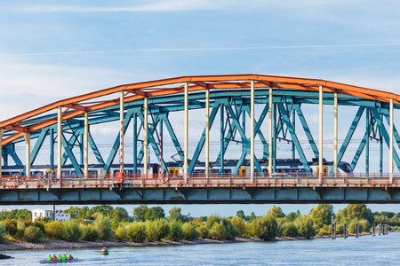 ZUTPHEN, NETHERLANDS - SEPTEMBER 28, 2015: Cyclists and train crossing the IJssel bridge during rush hour in Zutphen, The Netherlands
