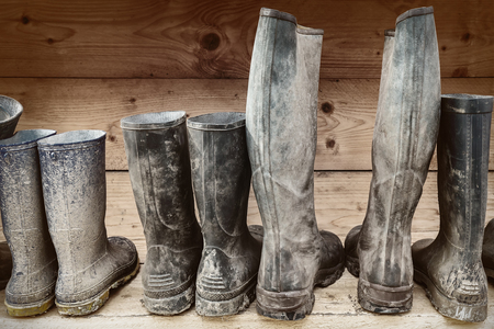 Row of muddy boots in front of a wooden wall