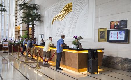 Foto de Shenzhen, China - Jun 14, 2016: Customers making check in procedure at the check in counter in lobby area of Grand Mercure Oriental Ginza Hotel. - Imagen libre de derechos