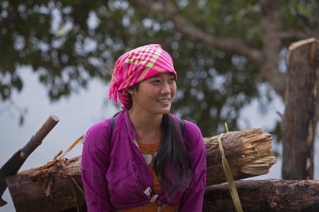 HA GIANG, VIETNAM - NOV 14, 2014: Close up portrait of an unidentified Hmong minority girl carrying fire wood home in Dong Van rocky plateau, far north of Vietnam.