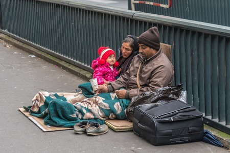 Photo for Homeless family sitting on the street - Royalty Free Image