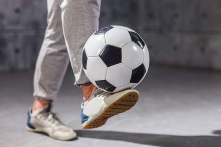 Man holds a soccer ball on his leg