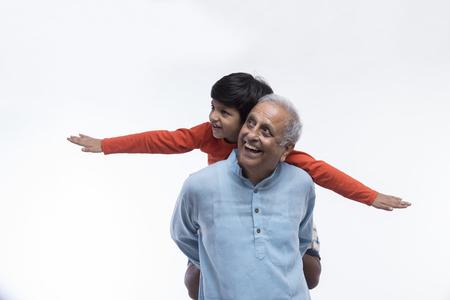 Photo pour Boy sitting on grandfather's shoulders pretending to be flying - image libre de droit