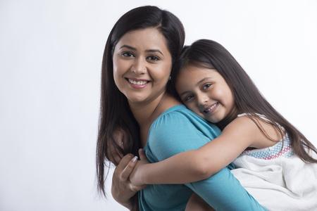 Photo pour Portrait of mother carrying daughter - image libre de droit
