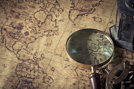 Magnifier with lantern with compass on the old map ,picture style vintage