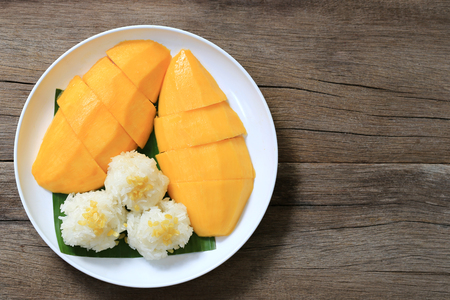 Photo pour Mango and sticky rice in white dish on wooden floor and have copy space,Dessert was popular in Thailand. - image libre de droit