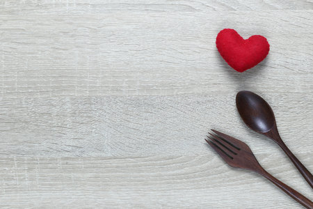 Photo pour Wooden spoon and dish and red heart on wooden floor with copy space in love or Valentine day concept. - image libre de droit
