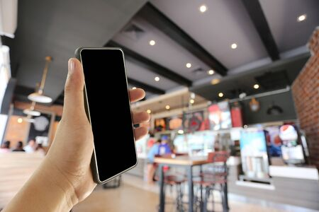 Photo pour Hand of a man holding smart phone device in the coffee cafe background and have copy space for design.  - image libre de droit