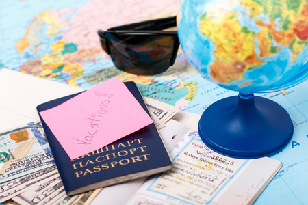 Passports money tickets globe and map of the world as a vacation concept. Summer journey preparation. Planning holidays cheking documents choosing destination point having fun.