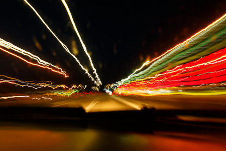 Drunken driving concept. Speedy night driving. Sleepy driver looking on night road. Drugs and alcohol effect. Blurry and blending road during high speed trip.
