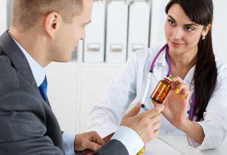 Beautiful female medicine doctor giving to male patient in business suit jar of pills. Antidepressant or man sexual potency cure. Medical and pharmacy concept. Businessman visiting therapeutist