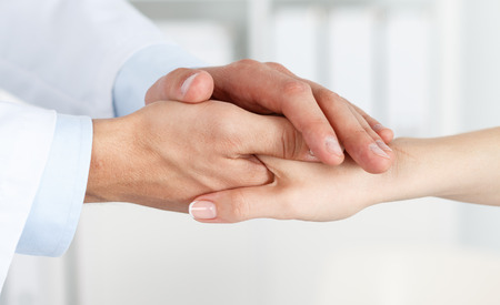Foto de Friendly male doctor's hands holding female patient's hand for encouragement and empathy. Partnership, trust and medical ethics concept. Bad news lessening and support. Patient cheering and support - Imagen libre de derechos