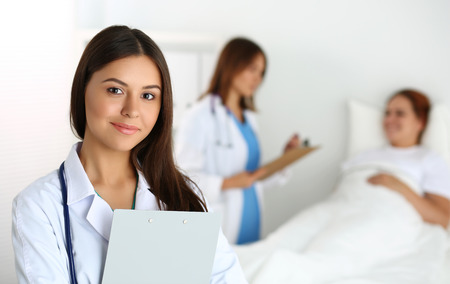 Beautiful female medicine doctor looking in camera in front of patient lying in bed and communicating with therapeutics.