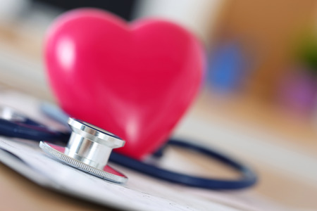 Foto de Medical stethoscope head and red toy heart lying on cardiogram chart closeup. Medical help, prophylaxis, disease prevention or insurance concept. Cardiology care, health, protection and prevention - Imagen libre de derechos