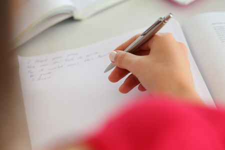 Female hand holding silver pen closeup. Woman writing letter, list, plan, making notes, doing homework. Student studying. Education, self development and perfection concept