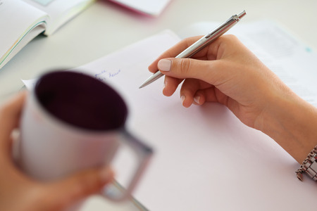 Photo pour Female hands holding cup of coffee or tea and silver pen closeup. Woman writing letter, list, plan, making notes, doing homework. Student studying. Education, self development and perfection concept - image libre de droit