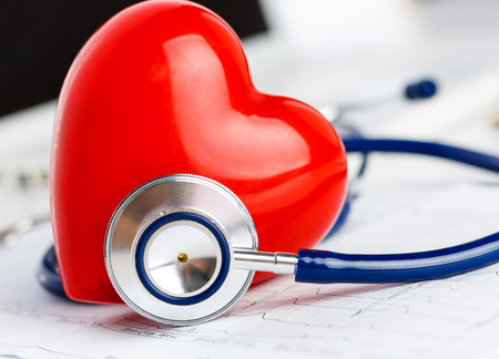 Foto de Medical stethoscope head and red toy heart lying on cardiogram chart closeup. - Imagen libre de derechos