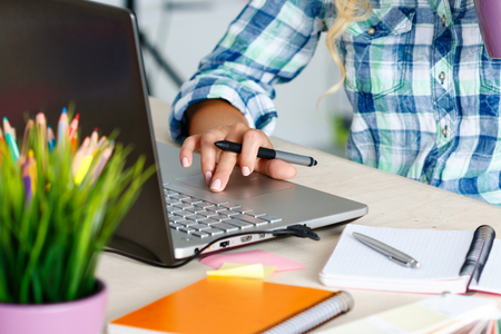 Hands of female designer in office working with digital graphic tablet and laptop. Photography retoucher sitting at desk and looking in display. Creative people or advertising business concept