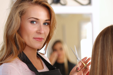 Beautiful blonde female hairdresser holding scissors in hands, picking proper hairdo to long haired customer and looking in camera. Hairdresser salon, barber shop, perfect look, new hairdo concept