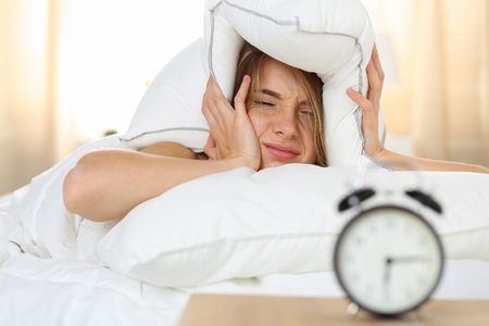 Photo pour Young beautiful blonde woman lying in bed suffering from alarm clock sound covering head and ears with pillow making unpleasant face. Early wake up, not getting enough sleep, going work concept - image libre de droit