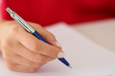 Photo pour Female hand holding silver pen closeup. Woman writing letter, list, plan, making notes, doing homework. Student studying. Education, self development and perfection concept - image libre de droit