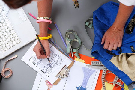 Photo pour Female fashion designer hands holding drawing pad and pen making sketch of new dress. Style and design development and creating garment, clothes sew and repair service, seamstress at work concept - image libre de droit