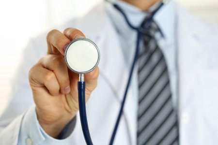 Male medicine doctor hand holding stethoscope head closeup in front of his chest. Healthy heart, eating and lifestyle, physician ready to examine patient, physical and disease prevention concept