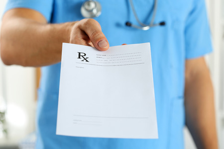 Photo for Male medicine doctor in blue uniform hold and give prescription to patient closeup. Panacea and life save, prescribe treatment, legal drug store, contraception concept. Empty form ready to be used - Royalty Free Image