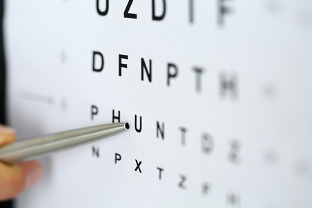 Foto de Silver ballpoint pen pointing to letter in eyesight check table. Sight test and correction, excellent vision or optician shop, laser surgery alternative, driver health certificate examination concept - Imagen libre de derechos