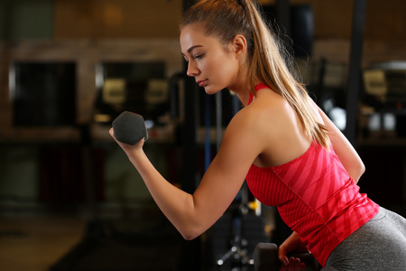 Sporty young woman work out biceps. Modern athletic trend, health care, heavy work, calorie burn diet, slim and power people, hobby and leisure activity, action wear shop, gain and pain concept
