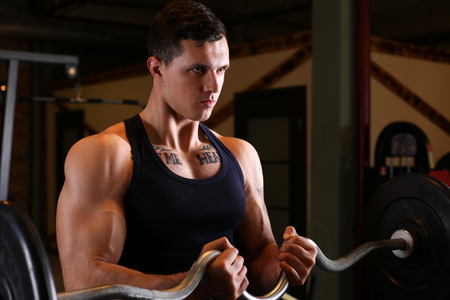 Sporty young man work out biceps. Modern athletic trend, health care, heavy work, calorie burn diet, slim and power people, hobby and leisure activity, action wear shop, gain and pain concept