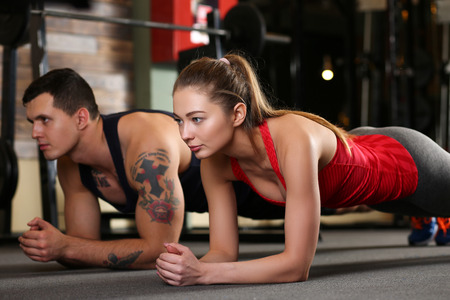Sporty young couple work out together. Modern athletic family support, health care, heavy work, calorie burn diet, slim and power people, hobby and leisure activity trend, action wear shop concept