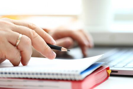 Photo pour Man holding in arm regular lead pencil while typing something at laptop pc closeup - image libre de droit