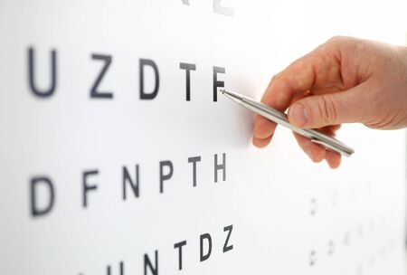 Photo pour Silver ballpoint pen pointing to letter in eyesight check table. Sight test and correction excellent vision or optician shop laser surgery alternative driver health certificate examination concept - image libre de droit